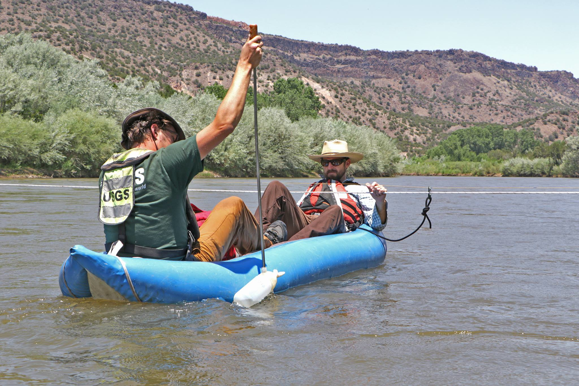 Two USGS employees, in a boat, sampling suspended sediment concentration in the Rio Grande River