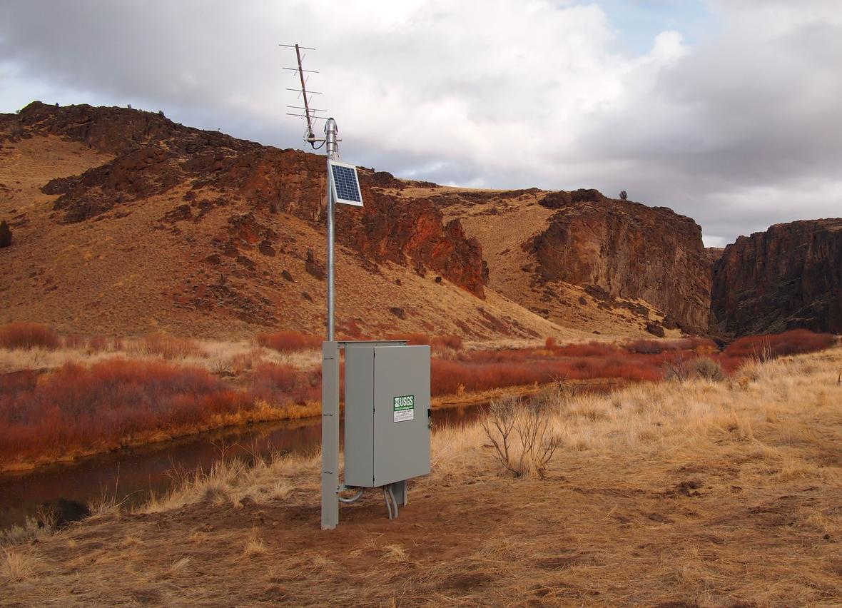 A photo of a streamgage on a riverbank in a canyon.