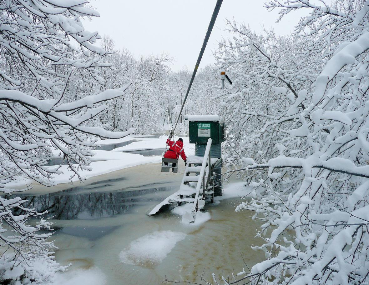 A man hangs from a cable car suspended over a river. He is moving towards a streamgage over the Roseau Rivernear Malun, MN.
