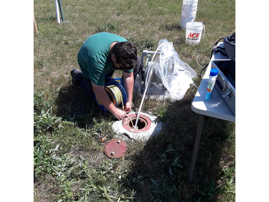 Picture of a person in the grass kneeling over a circular concrete wellhead, with instruments in the background